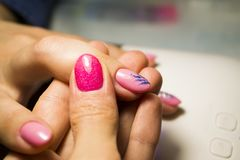 Manicure nail paint. Beautician applying nail polish to female n royalty free stock image