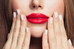 Manicure nails and red female lips.  royalty free stock photos