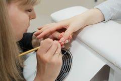 manicure O mestre faz a extens?o do prego: desenho do gel branco na borda livre de um prego foto de stock