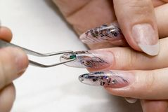Manicure one's nails. Effective manicure with semiprecious stones Royalty Free Stock Photo