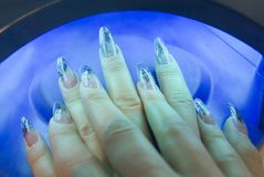 Manicure one's nails. Effective manicure with artificial nails in neon light Stock Photo