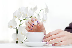 Manicure, orchid and coffee Stock Image
