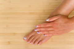 Manicure-Pedicure. A hand and a foot with nail art Stock Images
