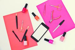 Manicure or pedicure equipment, nail polishes and smartphone. On colorful background Stock Photography