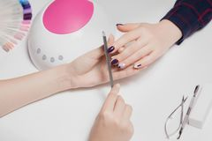 Manicure and pedicure. Woman removes manicure gel polish and skin care, nails in beauty salon. Concept fashion stock photography