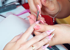 Manicure process in beauty salon - filling and polishing of nails Stock Photo