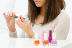 Manicure process at beauty spa and bottles of nail polish Royalty Free Stock Photography