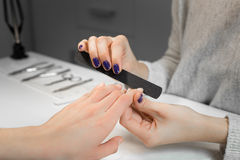 Manicure process with nail file in beauty salon Royalty Free Stock Photo