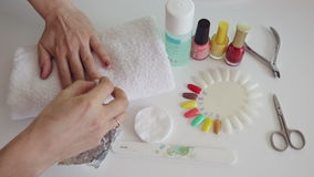 Manicure process in salon. Cleaning gel nail stock footage
