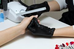 Manicure. Hands in black gloves cares about hands nails. Manicure beauty salon. Nails filing with file stock photo