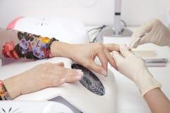 Manicure Prozess auf der weibliche Handfranzösischen Maniküre und machen Nagelextension Lizenzfreie Stockbilder
