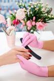 Manicure przy piękno salonem Mistrz trzyma client& x27; s ręk ręki w górę Różowe rękawiczki, czerwony gwoździa połysk fotografia royalty free