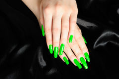 Manicure on real nails. Bright green manicure on actual long nails against black silk background Stock Photography