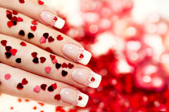 Manicure with a red heart. Beautiful holiday manicure with a red heart and with sparkles in the shape of a heart in my hand, and background stock images