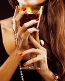 Manicure rosso sulle dita che giudicano di vetro con la vite Fotografie Stock Libere da Diritti