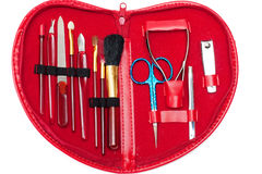 Manicure set. In red heart-shaped bag over white background Stock Images