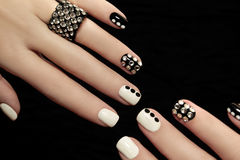 Manicure on short nails . Manicure on short nails covered with black and white lacquered with rhinestones on a black background Stock Image
