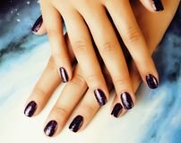 Manicure stylish concept: woman fingers with nails purple glitter on nails like cosmos, universe background royalty free stock images