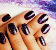 Manicure stylish concept: woman fingers with nails purple glitter on nails like cosmos, universe background Royalty Free Stock Image