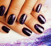 Manicure stylish concept: woman fingers with nails purple glitter on nails like cosmos, universe background Royalty Free Stock Photography