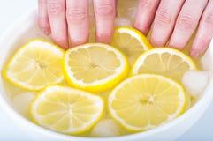 manicure Suco de limão, cosméticos naturais As unhas embebendo da mulher na água do suco de limão Fotografia de Stock