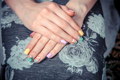 Manicure on the tablecloth of flowers Stock Images