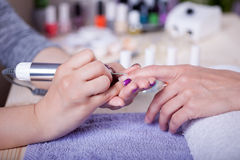 Manicure technician polishing fingernails by polish nail machine Royalty Free Stock Photo