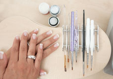 Manicure tools. Woman manicured nails with set of manicure tool brushes Royalty Free Stock Photography