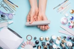 Manicure - tools for creating, gel polishes, all for nail care, beauty and care concept. On a blue background, hands with a. Manicure stock photo