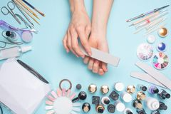 Manicure - tools for creating, gel polishes, all for nail care, beauty and care concept. On a blue background, hands with a. Manicure royalty free stock images