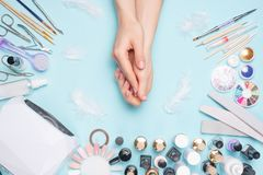 Manicure - tools for creating, gel polishes, all for nail care, beauty and care concept. On a blue background, hands with a. Manicure royalty free stock photos