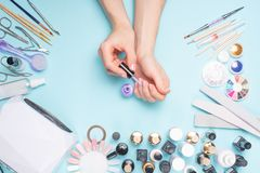 Manicure - tools for creating, gel polishes, all for nail care, beauty and care concept. On a blue background, hands with a. Manicure royalty free stock image