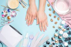 Manicure - tools for creating, gel polishes, all for nail care, beauty and care concept. On a blue background, hands with a. Manicure stock photography