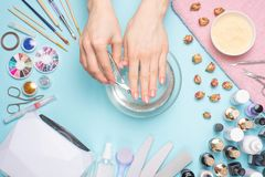 Manicure - tools for creating, gel polishes, all for nail care, beauty and care concept. On a blue background, hands with a. Manicure stock images