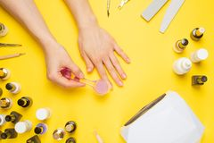 Manicure - tools for creating, gel polishes, all for nail care, beauty concept, care. On a yellow background, a woman gets a. Manicure of nails stock photo