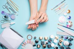 Manicure - tools for creating, gel polishes, care and hygiene for nails. Beauty salon, nail salon, mastira for working with nochts. Blue background royalty free stock photo