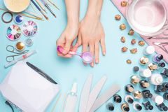 Manicure - tools for creating, gel polishes, care and hygiene for nails. Beauty salon, nail salon, mastira for working with nochts. Blue background stock photography