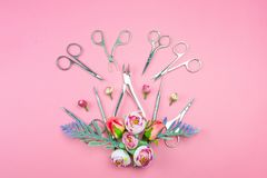 Manicure tools on a pink background decorated with flowers. stock photo