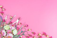 Manicure tools on a pink background decorated with flowers. royalty free stock image