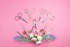 Manicure tools on a pink background decorated with flowers. royalty free stock photography