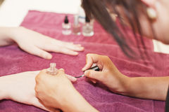 Manicure treatment in Beauty Spa Saloon. Applying nail polish Stock Images