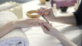 Manicure treatment at nail salon. Closeup shot of a woman in a nail salon receiving a manicure by a beautician with nail file. Woman getting nail manicure stock video