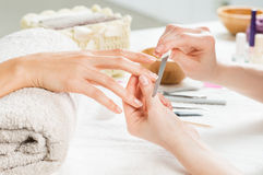 Manicure treatment at nail salon. Closeup shot of a women in a nail salon receiving a manicure by a beautician with nail file. Woman getting nail manicure royalty free stock image