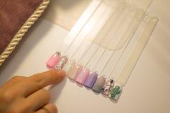 Manicure'u i gwoździa opieki pojęcie Kobieta w piękno salonu gwoździa chwyty barwiących próbnych połysk z różnymi kolorami i wybi fotografia stock