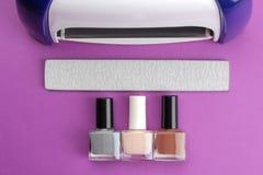 manicure UVlamp en nagelvijlen en nagellakken op een in purpere achtergrond Manicuretoebehoren en hulpmiddelen voor spijkers bove stock foto