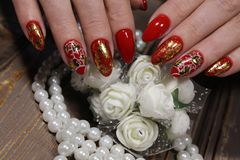 Manicure for Valentine& x27;s Day. Red with gold and heart royalty free stock photo