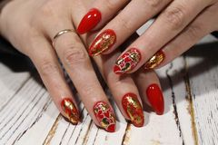Manicure for Valentine& x27;s Day. Red with gold and heart royalty free stock images