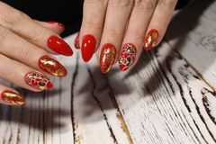 Manicure for Valentine& x27;s Day. Red with gold and heart stock image