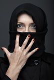 Manicure. Woman in black ninja dress with manicure royalty free stock photos