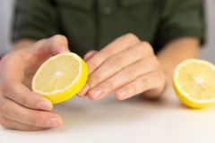 Manicure, woman cleans her nails with lemon. In a natural light royalty free stock image
